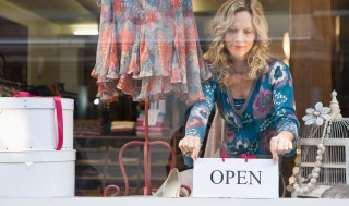 image of woman placing 'open' sign in store window